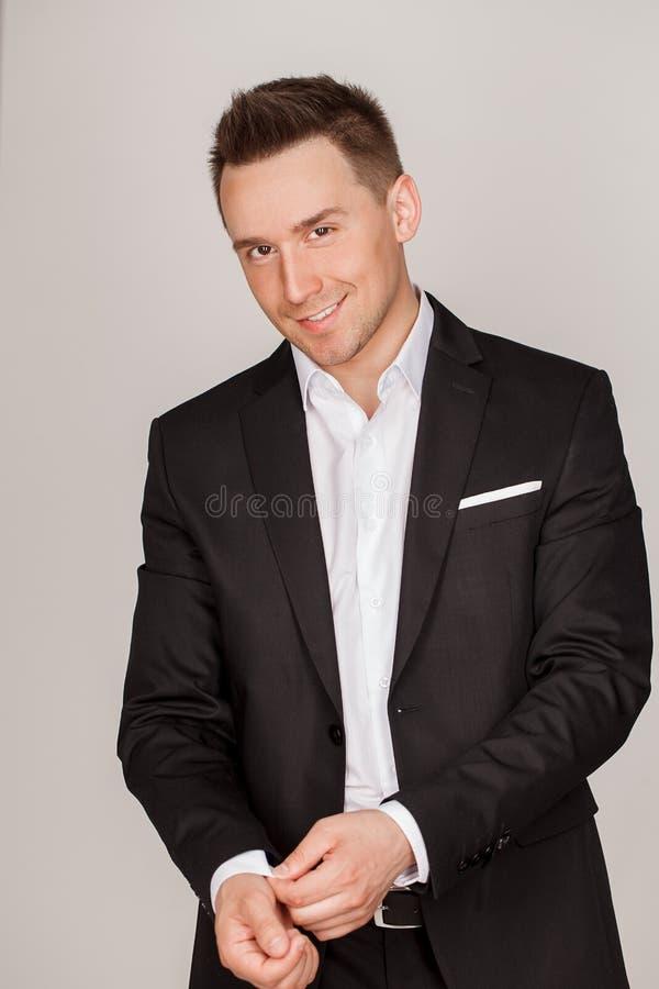 Un hombre joven hermoso elegante confiado que se coloca delante de un fondo gris en un estudio que lleva un traje agradable imagenes de archivo