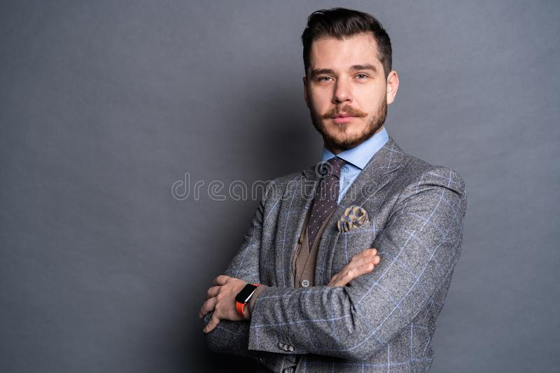 Un hombre joven hermoso elegante confiado que se coloca delante de un fondo gris en un estudio que lleva un traje agradable fotos de archivo