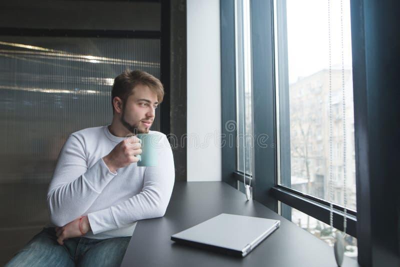 Un hombre joven hermoso que se sienta en una tabla con una taza de café cerca de un ordenador portátil cerrado durante una rotura fotografía de archivo libre de regalías