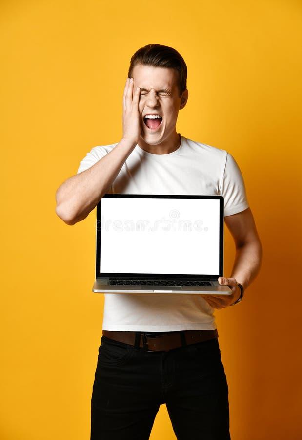 Un hombre joven hermoso que sostiene y que muestra la pantalla de un ordenador port?til foto de archivo libre de regalías