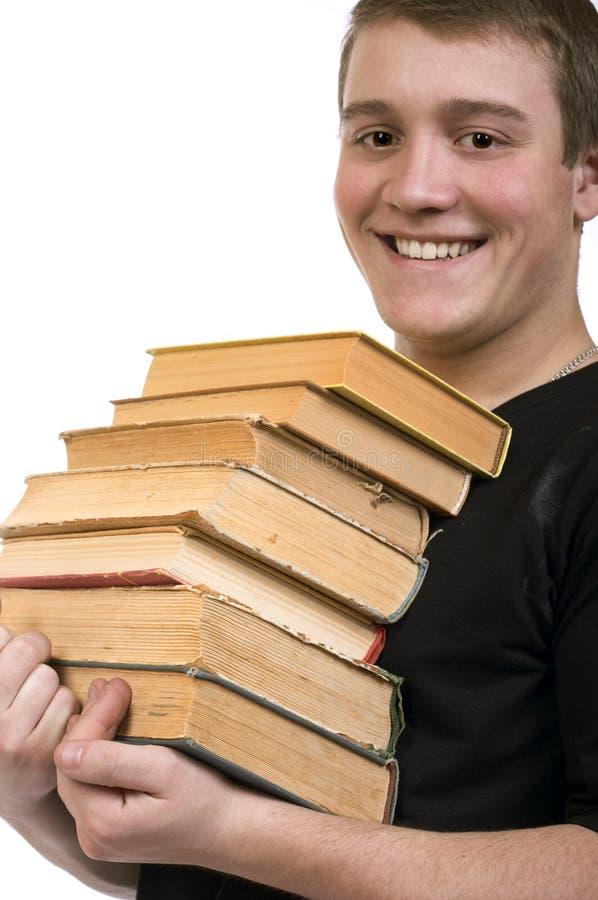 Un hombre joven lleva una pila de libros foto de archivo libre de regalías