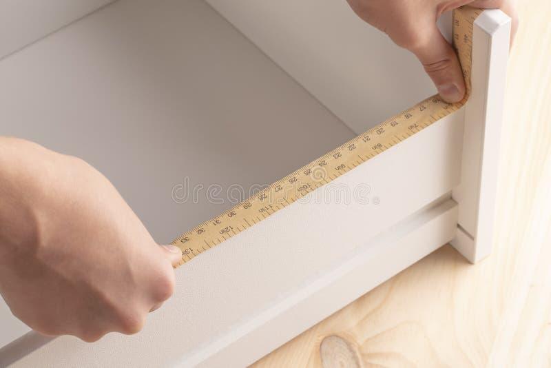 Un hombre joven mide los estantes con una herramienta de medición fotos de archivo