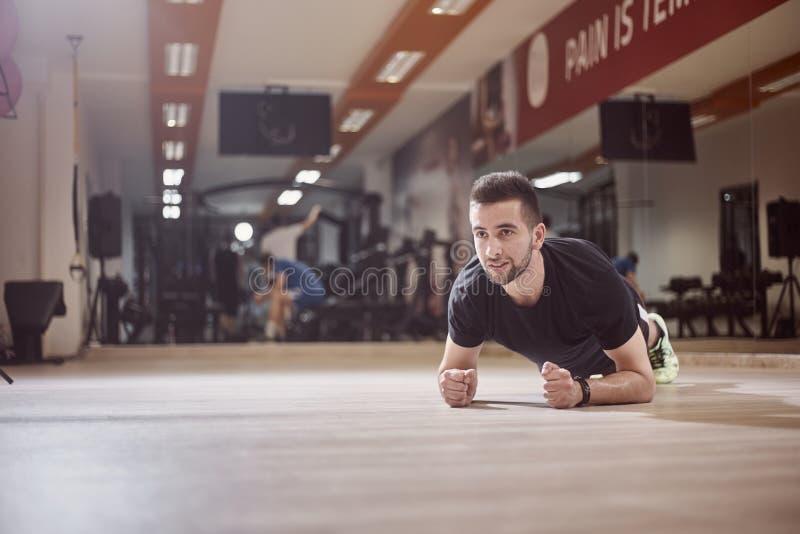 Un hombre joven, mirando lejos, ejercicio del tablón, piso del gimnasio, imagenes de archivo