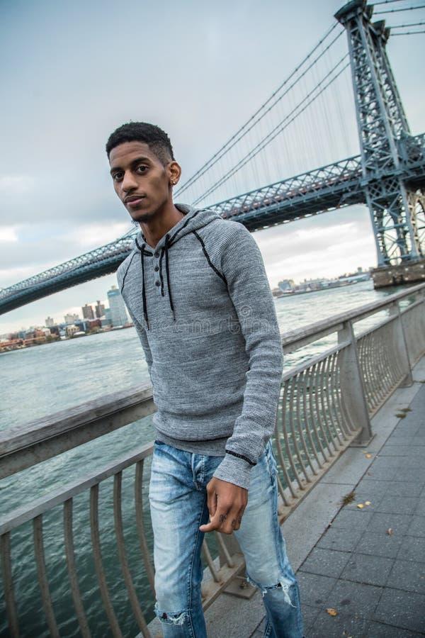 Un hombre joven, negro camina a lo largo del ` s East River - otoño 2016 de NYC fotografía de archivo
