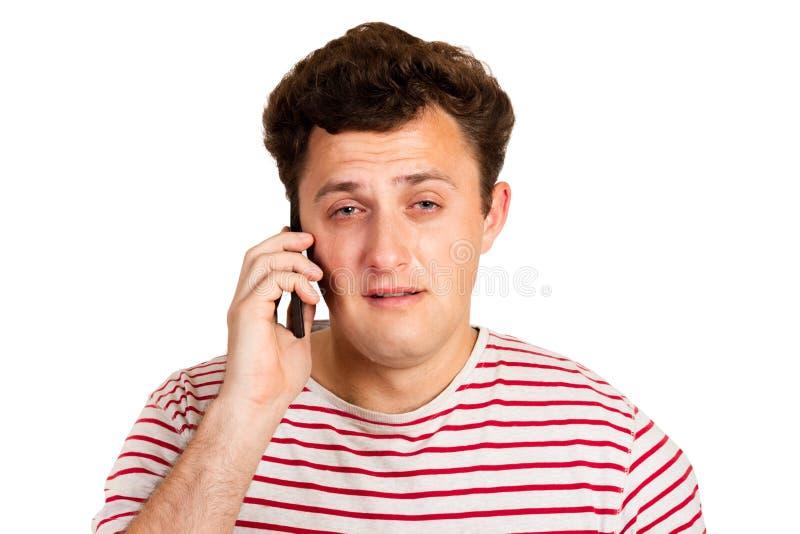 Un hombre joven oyó las malas noticias en el teléfono y comienza a llorar hombre emocional aislado en el fondo blanco foto de archivo libre de regalías