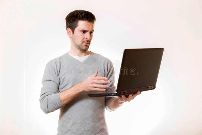 Un hombre joven parece desconfiado en su ordenador portátil imágenes de archivo libres de regalías