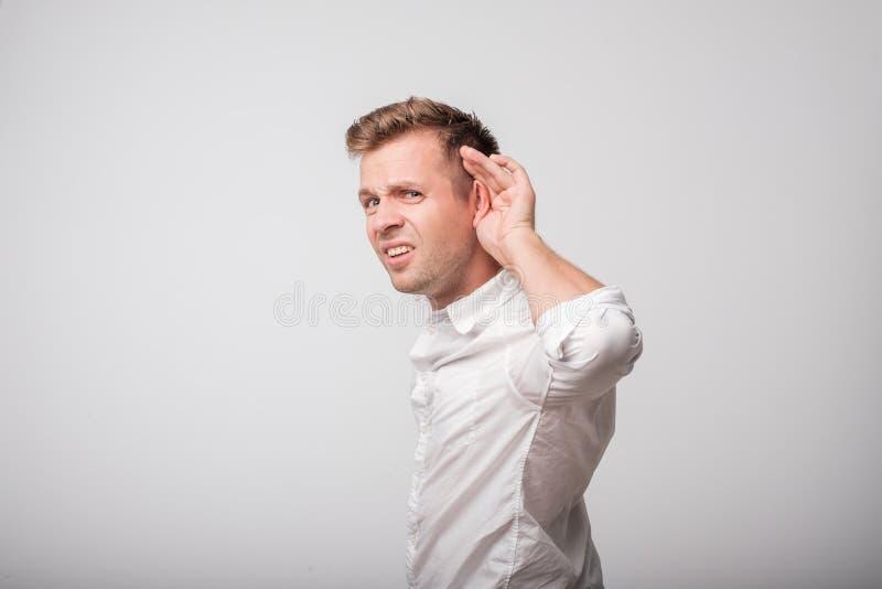 Un hombre joven pone una mano en el intento del oído para oír el susurro, aislado en un fondo blanco fotografía de archivo