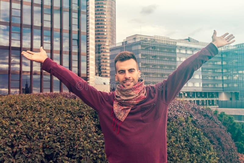 Un hombre joven que aumenta sus brazos, palmas abiertas en el centro de ciudad moderno - conceptos felices, del éxito y del logro fotografía de archivo