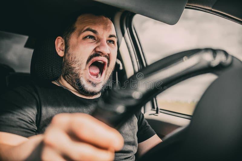 Un hombre joven que conduce un coche en gritos del choque por miedo a un accidente foto de archivo