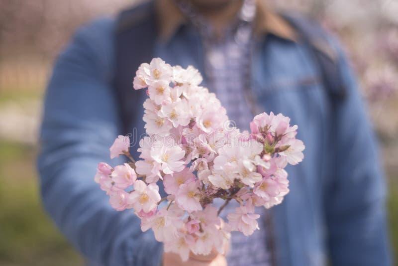 Un hombre joven que da el boquet de flores, de la primavera, del amor y de Roma rosados foto de archivo libre de regalías