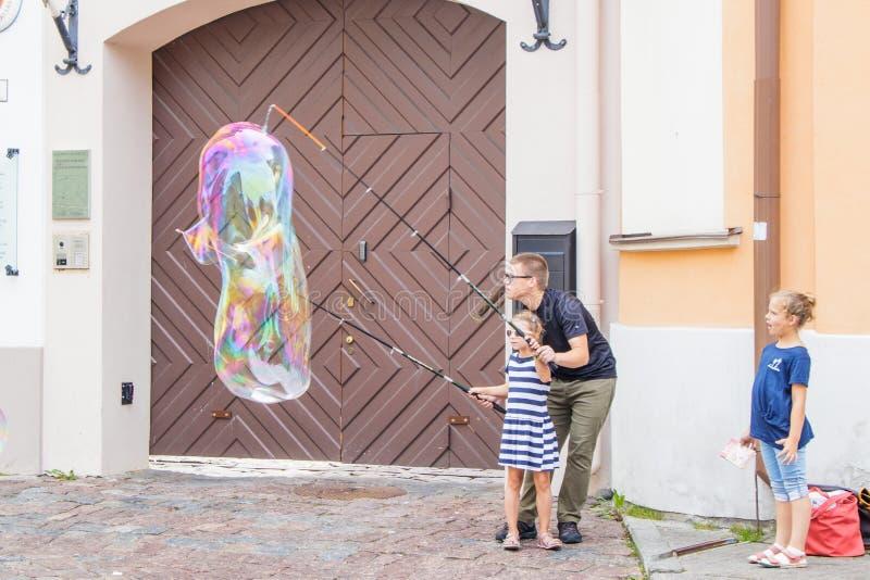 Un hombre joven que muestra a una muchacha una atracción con las cañas de pescar y las burbujas de jabón fotografía de archivo