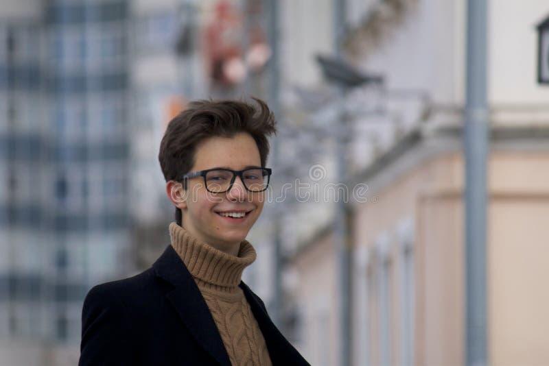 Un hombre joven que presenta con una sonrisa, entre el paisaje urbano Vestido en un abrigo ligero negro, vidrios negro-bordeados imagen de archivo libre de regalías