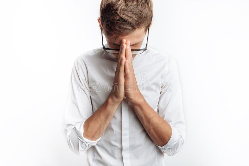 Un hombre joven que ruega a dios o a Jesus Christ, doblado, en un fondo blanco, pidiendo ayuda imágenes de archivo libres de regalías