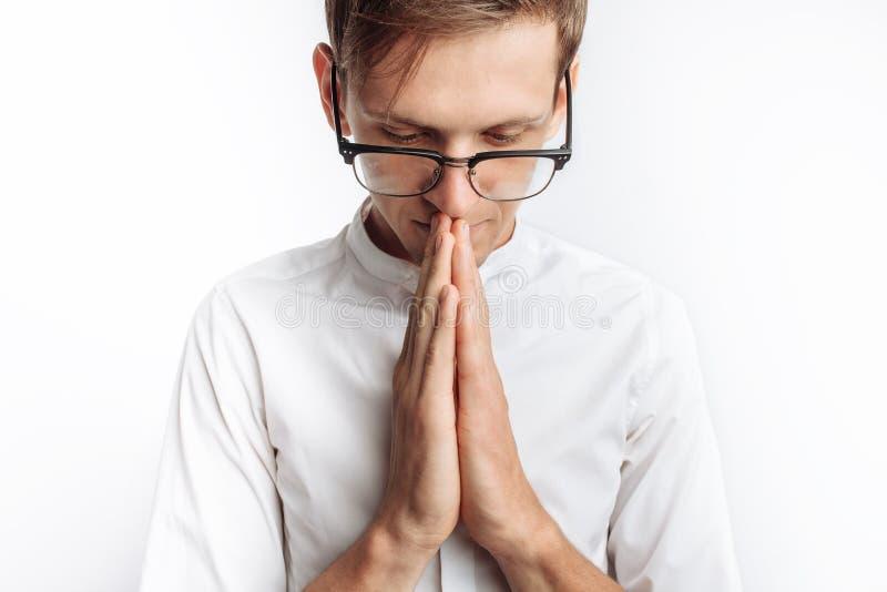 Un hombre joven que ruega a dios o a Jesus Christ, doblado, en un fondo blanco, pidiendo ayuda imagen de archivo