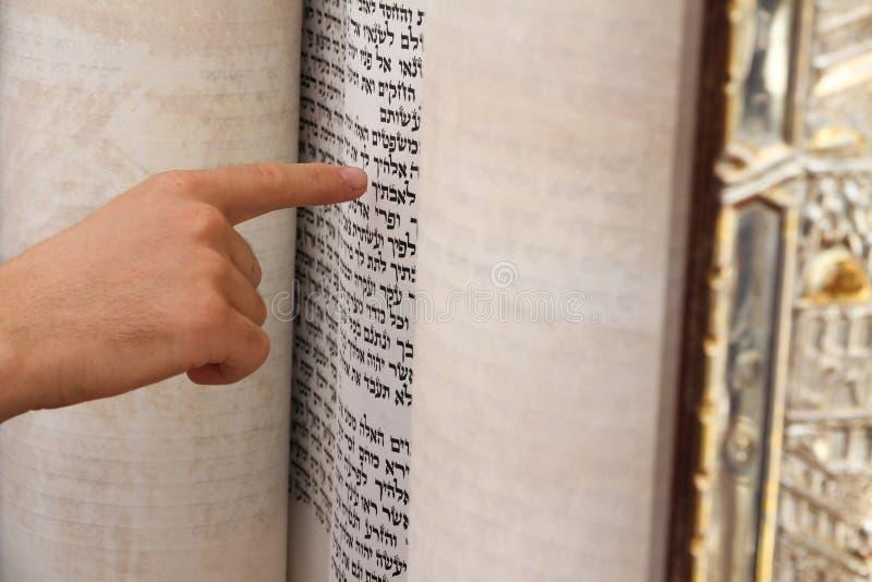 Un hombre joven que señala en una frase en un libro de la biblia imagen de archivo