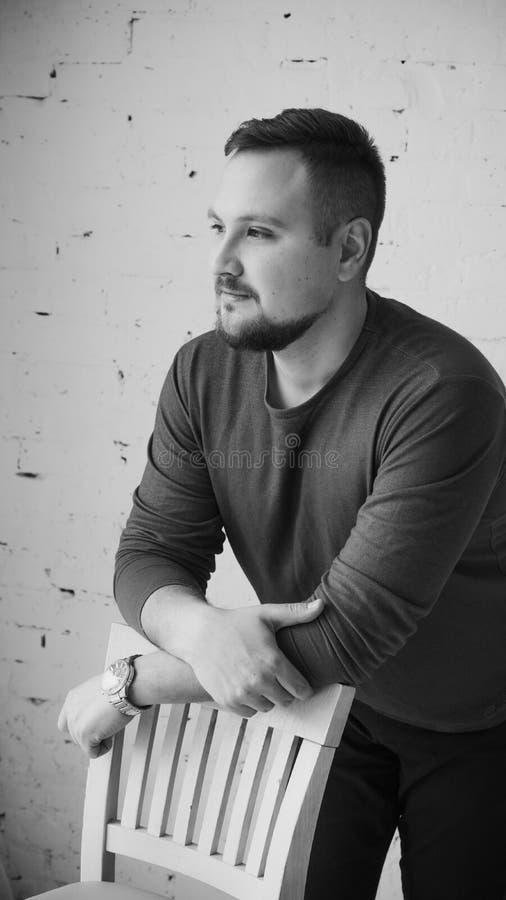 Un hombre joven que se inclina en la parte de atrás de una silla mira al lado contra una pared de ladrillo blanca Foto blanco y n foto de archivo
