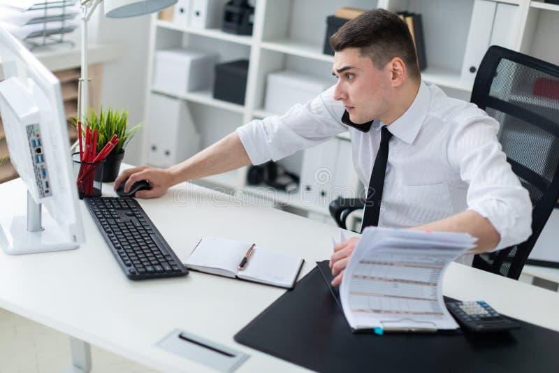 Un hombre joven que se sienta en una tabla en la oficina, hablando en el teléfono y trabajando con un ordenador y los documentos fotos de archivo