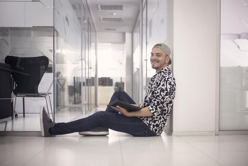 Un hombre joven que sonríe, 20-29 años, sentándose en piso, espacio de oficina, interior moderno ropa casual, actitud de relajaci imágenes de archivo libres de regalías