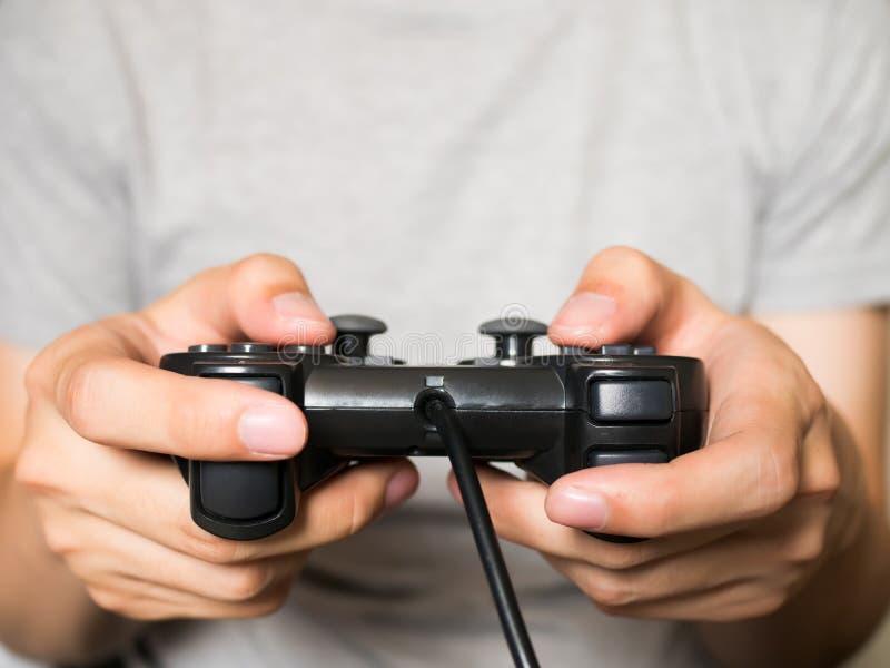 Un hombre joven que sostiene el regulador del juego que juega a los videojuegos fotografía de archivo libre de regalías