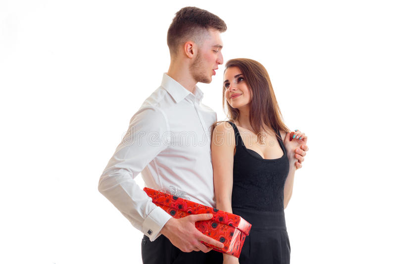 Un hombre joven que sostiene un regalo para su hembra aislada en un fondo blanco fotos de archivo