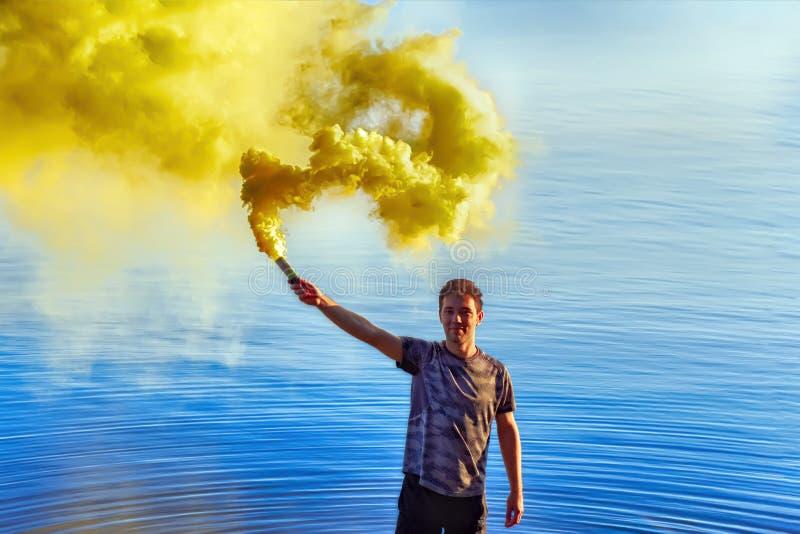Un hombre joven que sostiene una bomba de humo Humo coloreado fotos de archivo libres de regalías