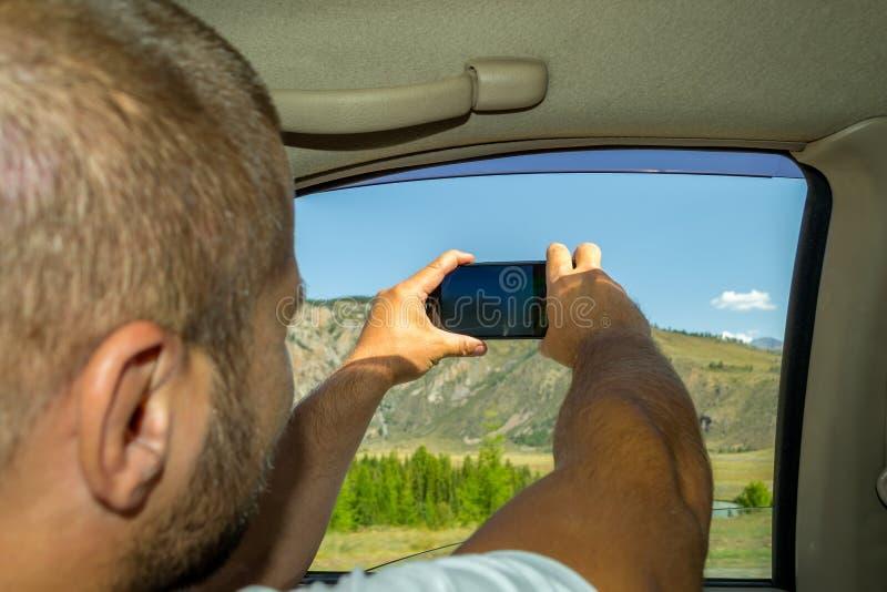 Un hombre joven que tira de la mano melenuda en la ventana imagen de archivo