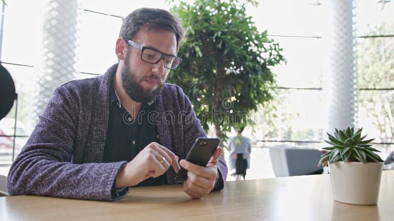 Un hombre joven que usa Smartphone en el café fotografía de archivo libre de regalías