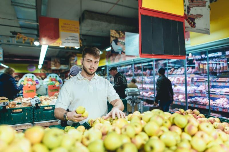 Un hombre joven recolecta manzanas de los estantes de una tienda Un hombre compra fruta en el departamento vegetal del supermerca fotos de archivo libres de regalías