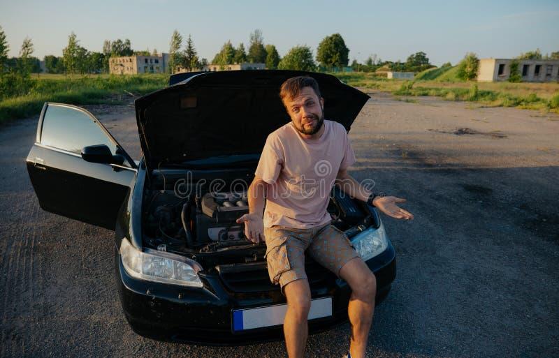 Un hombre joven repara un coche en la puesta del sol fuera de la ciudad foto de archivo