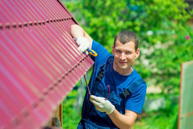 Un hombre joven repara el tejado de la casa en guardapolvos imagen de archivo