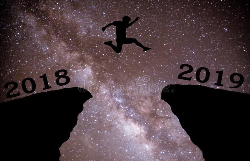 Un hombre joven salta entre 2018 y 2019 años sobre el cielo nocturno con las estrellas y a través en el hueco de la tarde de la s imagenes de archivo