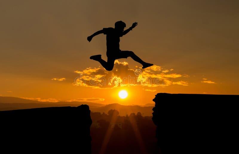 Un hombre joven salta entre 2017 y 2018 años sobre el sol y a través en el hueco de la silueta de la colina que iguala el cielo c imagenes de archivo