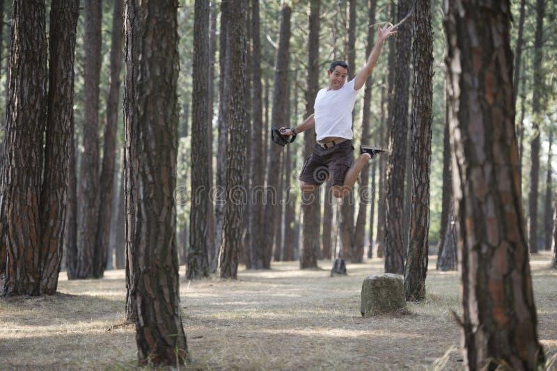 Un hombre joven salta a través de los árboles imagen de archivo libre de regalías