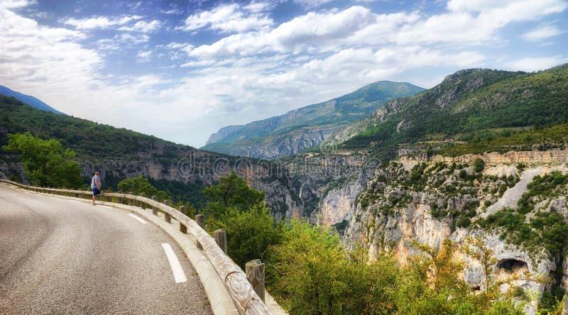 Un hombre joven se coloca al borde de un camino de la montaña y admira el panorama de las montañas foto de archivo libre de regalías