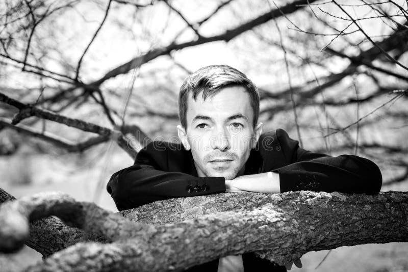 Un hombre joven se inclinó en la rama del árbol Puse mi cabeza en mis codos fotos de archivo