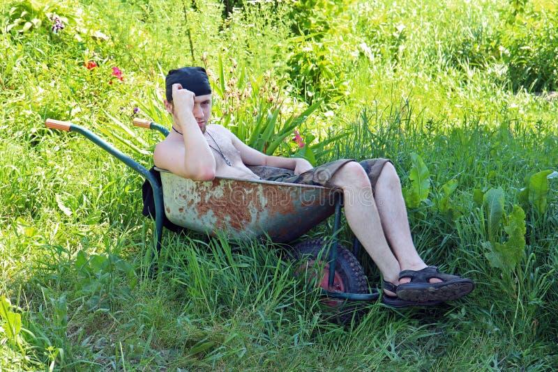 Un hombre joven se sienta en una carretilla oxidada en el jardín en un día soleado fotos de archivo libres de regalías