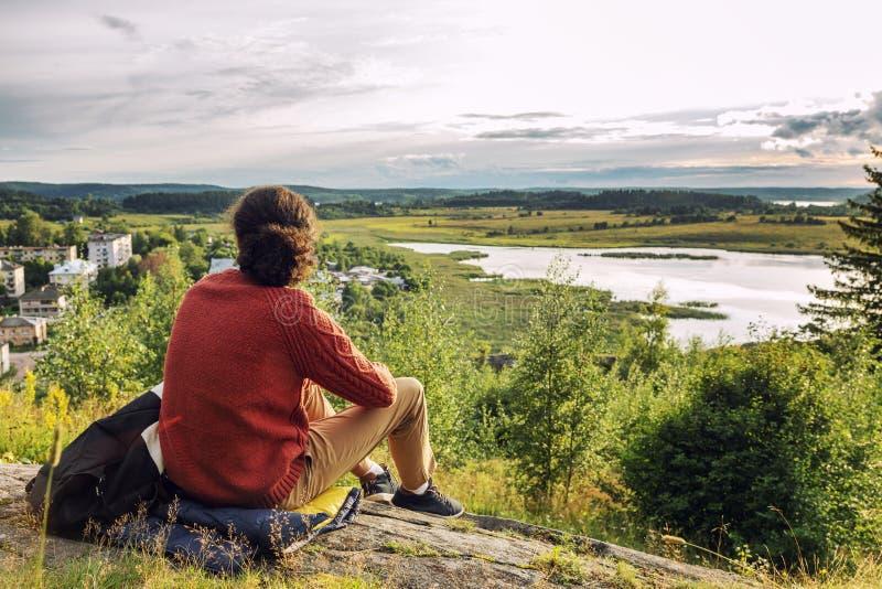Un hombre joven se sienta en una colina y disfruta de la naturaleza y de la puesta del sol Paisaje hermoso imágenes de archivo libres de regalías