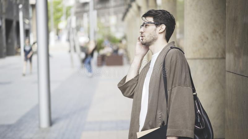 Un hombre joven se vistió en ropa casual que hablaba en el teléfono imagen de archivo libre de regalías