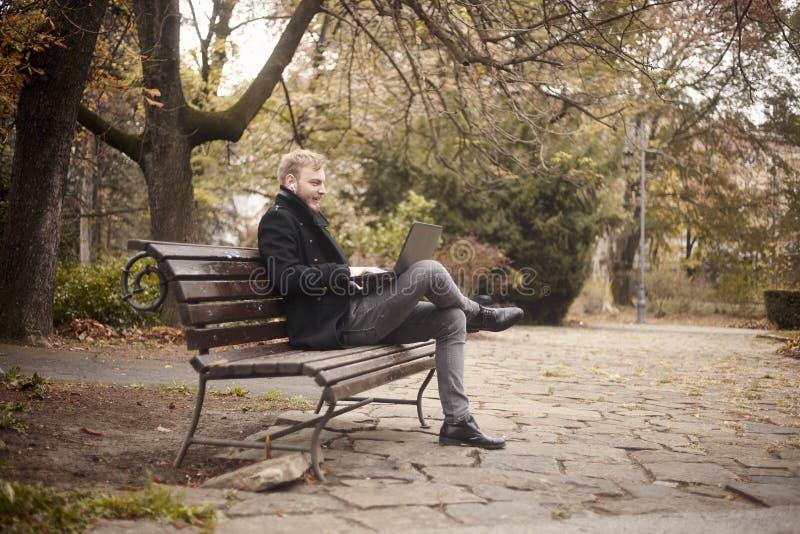 Un hombre joven, sent?ndose en banco en parque p?blico, usando el ordenador port?til, hablando sobre Internet, la charla o la lla imagenes de archivo