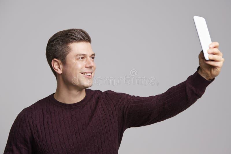 Un hombre joven sonriente que toma un selfie con su smartphone imagenes de archivo