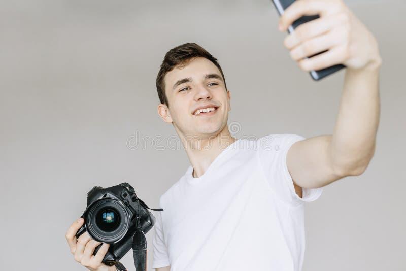 Un hombre joven sostiene una cámara de la foto en su mano y hace un selfie por el teléfono Fondo gris aislado imagen de archivo
