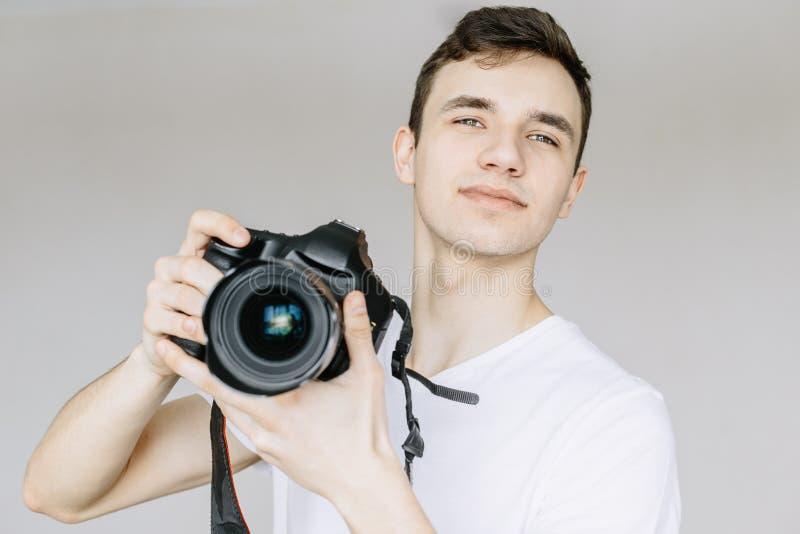 Un hombre joven sostiene una cámara de la foto en su mano y mira derecho Fondo gris aislado foto de archivo libre de regalías