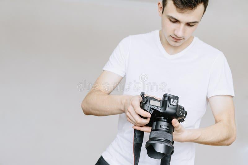 Un hombre joven sostiene una cámara de la foto en su mano y miradas en la foto en la cámara de la foto Fondo gris aislado imágenes de archivo libres de regalías