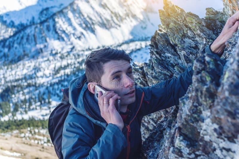 Un hombre joven sube la montaña al top y a hablar sosteniendo el teléfono Concepto de logro de la persistencia y de la meta foto de archivo libre de regalías