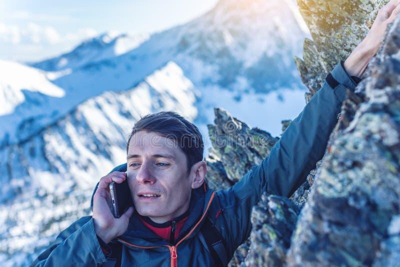 Un hombre joven sube la montaña al top y a hablar sosteniendo el teléfono Concepto de logro de la persistencia y de la meta imagen de archivo libre de regalías