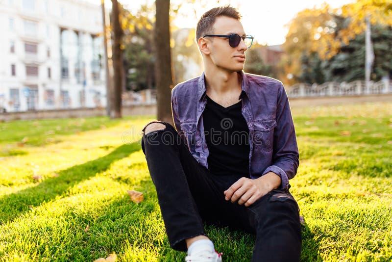 Un hombre joven, vestido en ropa casual, se sienta en un parque en el la fotografía de archivo