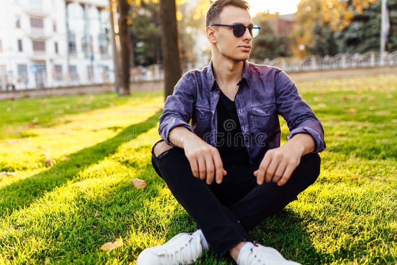 Un hombre joven, vestido en ropa casual, se sienta en un parque en el la fotos de archivo libres de regalías