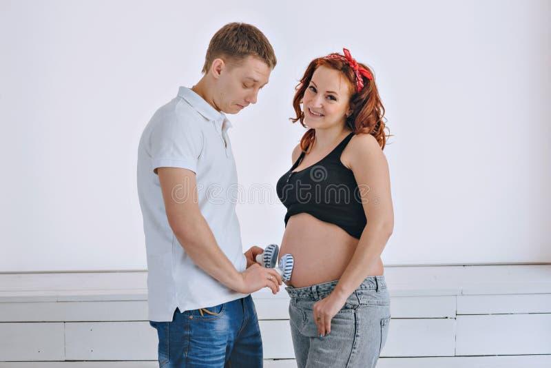 Un hombre joven y una mujer hermosa joven que miran uno a Antes del bebé Mujer pelirroja embarazada fotografía de archivo libre de regalías