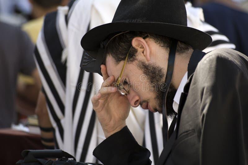 Un hombre judío vestido negro que ruega en la pared que se lamenta en Jerusalén foto de archivo