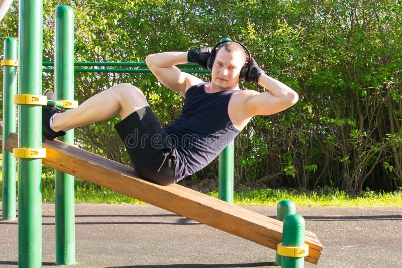 Un hombre juega deportes en el aire abierto, escucha la música, en una plataforma especial, hace un ejercicio en una prensa y mir fotografía de archivo